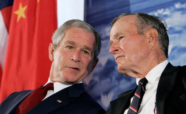 FILE PHOTO: U.S. President George W. Bush (L) speaks to his father, former U.S. President George H.W. Bush, during the dedication of the new U.S. embassy in Beijing August 8, 2008. Reuters
