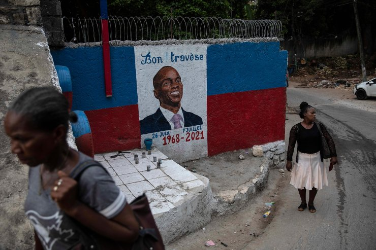 Women walk next to a mural with the portrait of the assassinated president of Haiti Jovenel Moïse in Port-au-Prince, Haiti, Wednesday, Sept. 22, 2021. AP