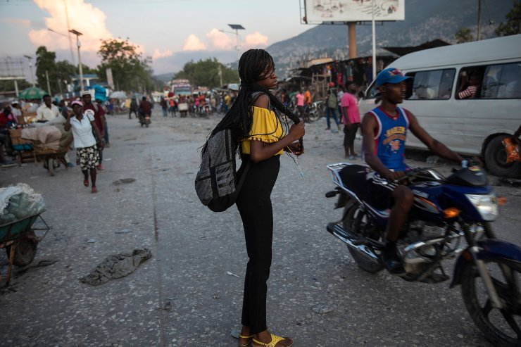 A woman waits for a public transportation in downtown Port-au-Prince, Haiti, late afternoon, Tuesday, Sept. 21, 2021. AP