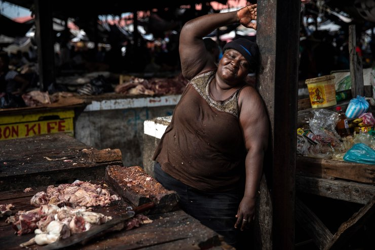 Vendor Celestine poses for a photo while taking a break in her butcher stand in a popular market in downtown Port-au-Prince, Haiti, Wednesday, Sept. 22, 2021. AP