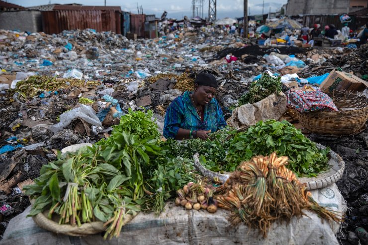 A woman selling greens waits for customers in the Croix des Bosalles market in Port-au-Prince, Haiti, Wednesday, Sept. 22, 2021. The floor of the market is thick with decomposing trash and, in some places, small fires of burning trash. AP