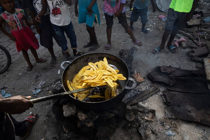 A vendor fries a batch of plantains at a market in the La Saline neighborhood near the main port entrance, partially burned by a gang two years ago, in Port-au-Prince, Haiti, Monday, Sept. 13, 2021. There could be as many as 100 gangs in Port-au-Prince; no one has an exact count and allegiances often are violently fluid. AP