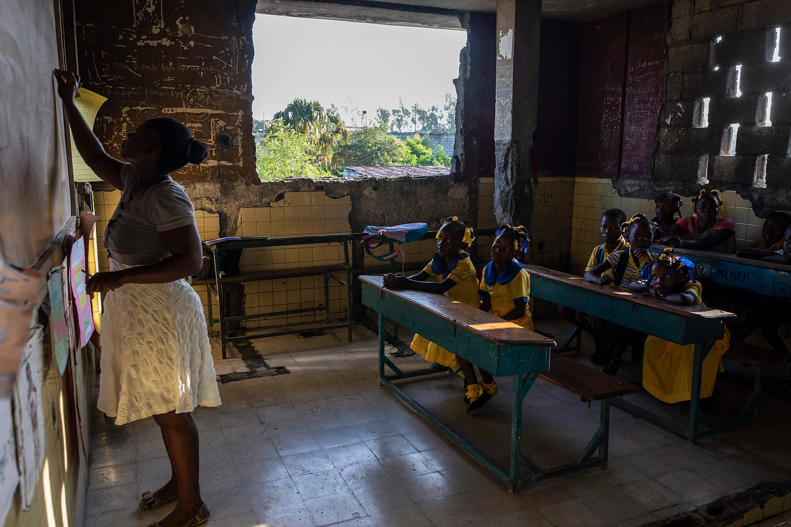 A teacher writes on a blackboard during a class in Sante Bernadette school, inside Fort Dimanche, once a prison where the late Haitian dictator Francois 'Papa Doc' Duvalier imprisoned his enemies in Port-au-Prince, Haiti, Thursday, Sep. 23, 2021. AP