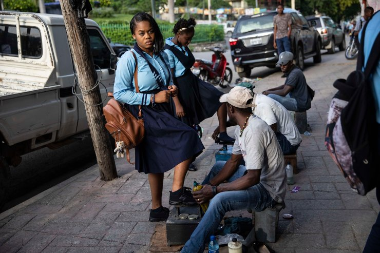 A man shines a student's shoes before entering to Lycée National school in the Petion Ville district of Port-au-Prince, Haiti, Monday, Sept. 27, 2021. AP