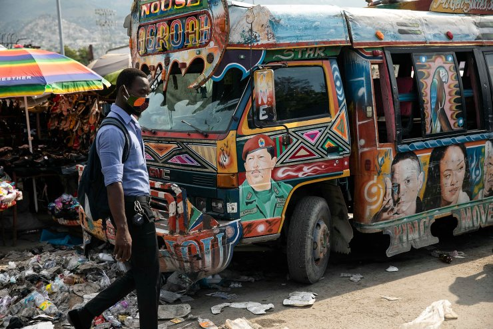 A man walks past to a public bus featuring a portrait of the late Venezuelan President Hugo Chavez in downtown Port-au-Prince, Haiti, Friday, Sept. 24, 2021. AP