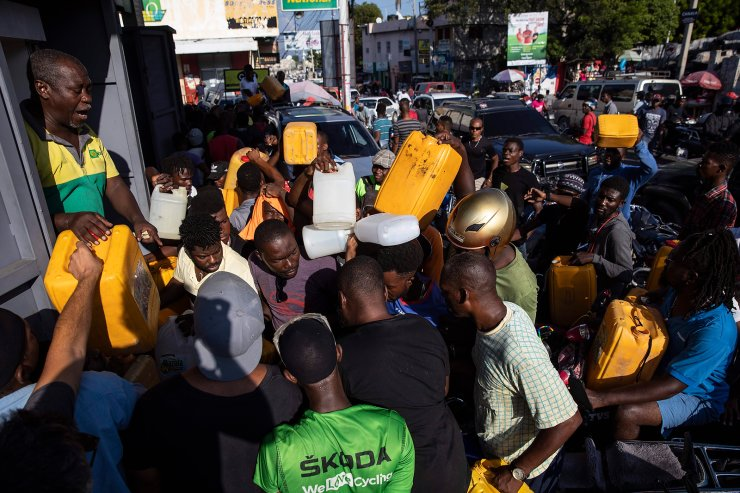 People push and shove as they try to get their tanks filled with gasoline at a gas station in Port-au-Prince, Haiti, Saturday, Sept. 25, 2021. AP