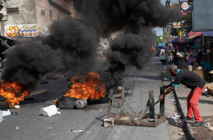 A man blocks an avenue with a table during a protest organized by friends and relatives of Biana Velizaire, who was kidnapped and held for several days by gang members, in Port-au-Prince, Haiti, Monday, Sept. 27, 2021. AP