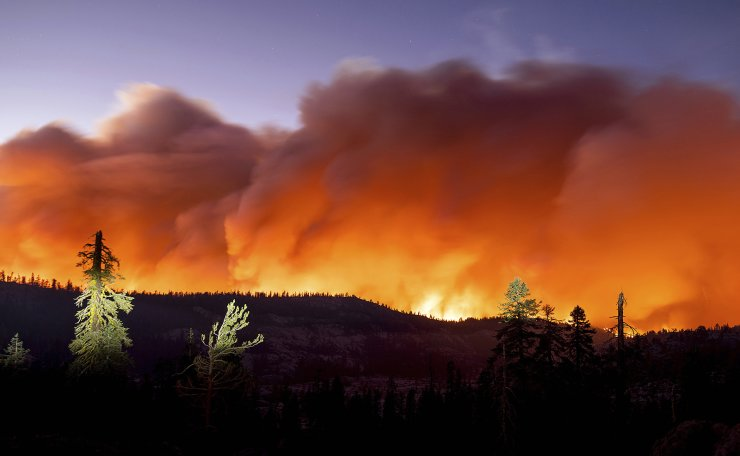 In this Sunday, Aug. 29, 2021 file photo, the Caldor Fire burns in Eldorado National Forest, Calif. Last week, managers overseeing the fight against the massive wildfire scorching California's Lake Tahoe region thought they could have it contained by the start of this week. Instead, on Monday, Aug. 30, 2021, the Caldor Fire crested the Sierra Nevada, forcing the unprecedented evacuation of all 22,000 residents of South Lake Tahoe. AP