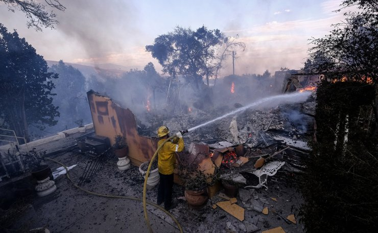 In this Aug. 25, 2021, file photo a firefighter tries to extinguish the flames at a burning house as the South Fire burns in Lytle creek, San Bernardino County north of Rialto, Calif.  In a season of daunting wildfires and flooding, the Biden administration is taking an initial step to assess how climate change could harm financial markets, planning to launch a 75-day comment period Tuesday, Aug. 31, on how the impacts could reshape the insurance sector. AP