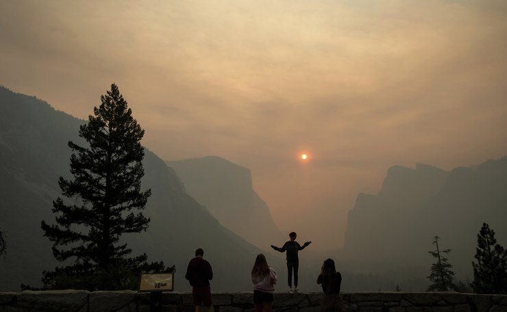 In this July 25, 2018 file photo, Hannah Whyatt poses for a friend's photo as smoke from the Ferguson Fire fills Yosemite Valley in Yosemite National Park, Calif. Wildfires burning in the U.S. this summer have upended plans for countless outdoor adventures. Campers, hikers, rafters and other outdoor enthusiasts have had to scrap or change plans or endure awful smoke. AP