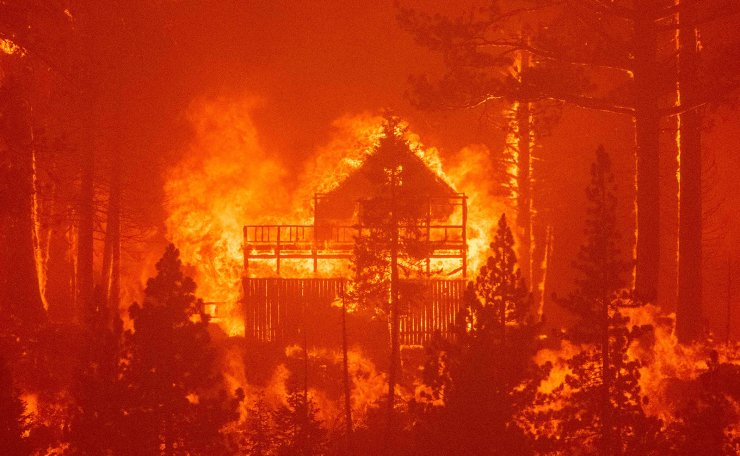 Flames consume multiple homes as the Caldor fire pushes into South Lake Tahoe, California on August 30, 2021. - At least 650 structures have burned and thousands more are threatened as the Caldor fire moves into the resort community of South Lake Tahoe, California. Thousands of people were ordered to evacuate Monday as a huge wildfire loomed over a major US tourist spot, filling the air with choking smoke. The Caldor Fire has already torn through more than 270 square miles (700 square kilometers), razing hundreds of buildings.  AFP