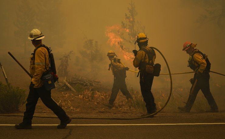 Firefighters carry water hoses while battling the Caldor Fire near South Lake Tahoe, Calif., Tuesday, Aug. 31, 2021. A huge firefighting force gathered Tuesday to defend Lake Tahoe from the raging wildfire that forced the evacuation of California communities on the south end of the alpine resort and put others across the state line in Nevada on notice to be ready to flee. AP