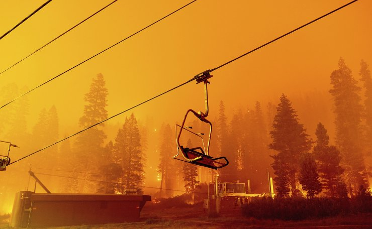 In this Sunday, Aug. 29, 2021 file photo, the Caldor Fire burns as a chair lift sits at the Sierra-at-Tahoe ski resort in Eldorado National Forest, Calif. The main buildings at the ski slope's base survived as the main fire front passed. Last week, managers overseeing the fight against the massive wildfire scorching California's Lake Tahoe region thought they could have it contained by the start of this week. Instead, on Monday, Aug. 30, 2021, the Caldor Fire crested the Sierra Nevada, forcing the unprecedented evacuation of all 22,000 residents of South Lake Tahoe. AP