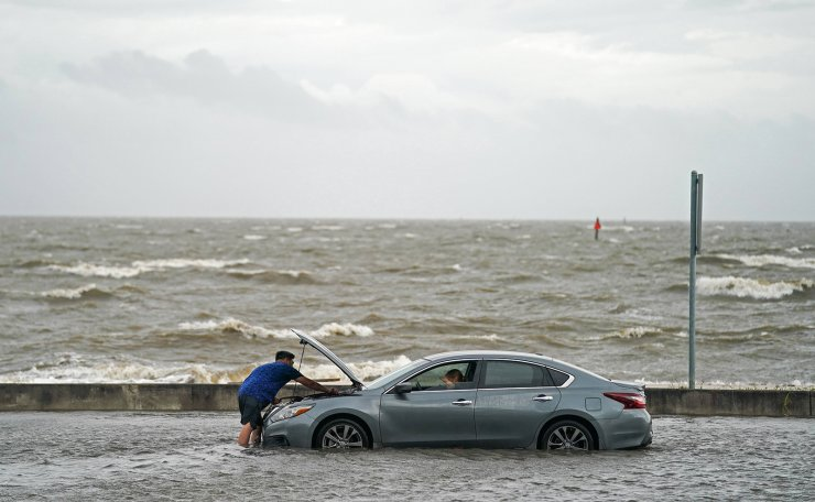 A man helps a stranded motorist in floodwaters on Beach Blvd. on August 30, 2021 in Biloxi, Mississippi. Tropical Storm Ida made landfall as a Category 4 hurricane yesterday in Louisiana and brought flooding and wind damage along the Gulf Coast. AFP