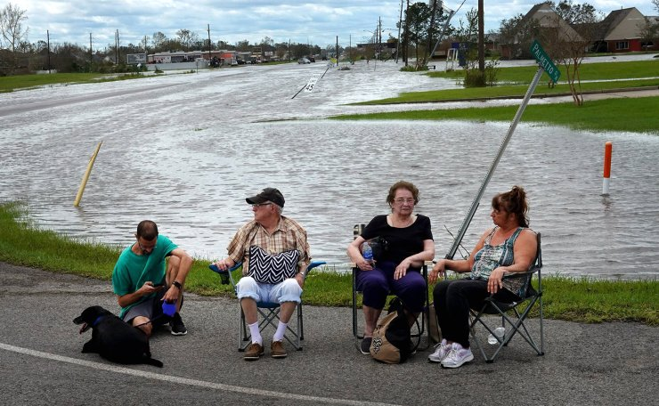People wait for transportation after being rescued from a flooded neighborhood in the aftermath of Hurricane Ida on August 30, 2021 in Laplace, Louisiana. Ida made landfall August 29, as a category 4 storm southwest of New Orleans. AFP