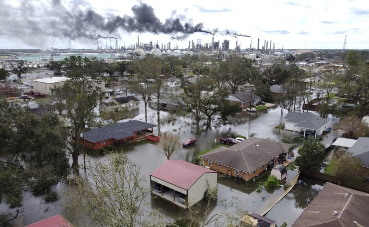 Homes near Norco, La., are surrounded by floodwater as chemical refineries continue to flare the day after Hurricane Ida hit southern Louisiana, Monday, Aug. 30, 2021. AP