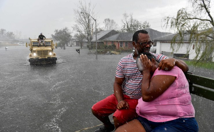 People react as a sudden rain shower soaks them with water while riding out of a flooded neighborhood in a volunteer high water truck assisting people evacuating from homes after neighborhoods flooded in LaPlace, Louisiana on August 30, 2021 in the aftermath of Hurricane Ida. AFP