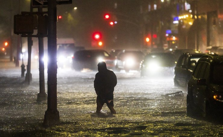 A man navigates a street flooded by heavy rain as remnants of Hurricane Ida hit the area in the Queens borough of New York, New York, USA, 01 September 2021. EPA