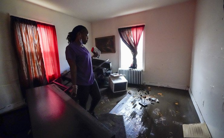 Melissa Weekes searches her flooded apartment for salvageable items, Friday, Sept. 3, 2021, in Mamaroneck, N.Y. More than three days after the hurricane blew ashore in Louisiana, Ida's rainy remains hit the Northeast with stunning fury on Wednesday and Thursday, submerging cars, swamping subway stations and basement apartments and drowning scores of people in five states. AP