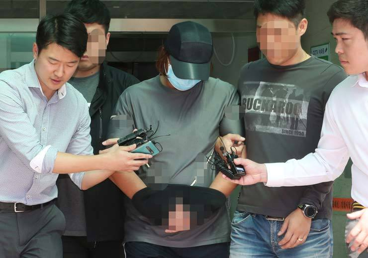 Reporters ask a murder suspect questions as he leave the police station in Michuhol-gu, Incheon, Sunday, for interrogation at the Incheon District Court. / Yonhap