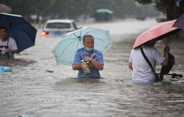 Residents wade through floodwaters on a flooded road amid heavy rainfall in Zhengzhou, Henan province, China, July 20. Reuters-Yonhap