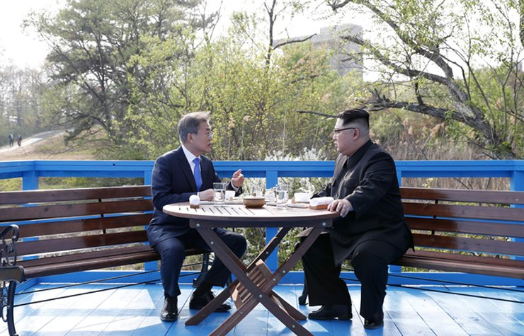 President Moon Jae-in, left, and North Korea's leader Kim Jong-un speak in private during their first summit held at the truce village of Panmunjeom, April 27, 2018.