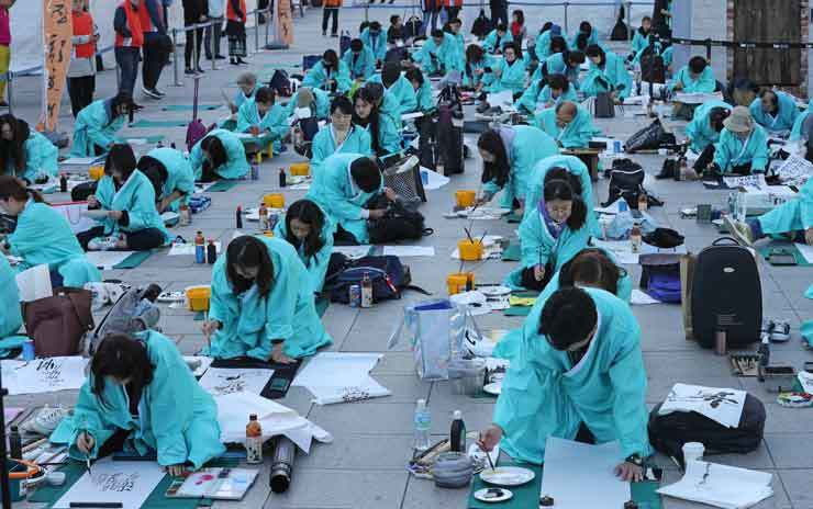 Participants in the 10th Korean Calligraphy Contest write Korean letters in Gwanghwamun Square in central Seoul, Wednesday, the 573rd anniversary of the promulgation of the Korean alphabet, Hangeul, first created in 1443 by King Sejong. In a congratulatory text message, President Moon-Jae-in lauded
