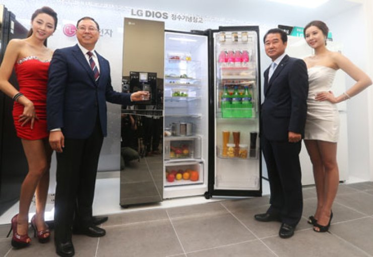 Cho Sung-jin, second from left, head of LG Electronics' home appliance division, poses with Choi Sang-kyu, third from left, head of the company'sKorean marketing division, and models during a launch event to unveil its new refrigerator at the company's headquarters in Yeouido, northern Seoul,Wednesday. / Courtesy of LG Electronics