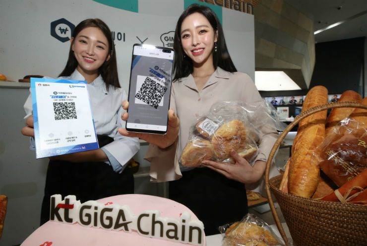 Models show off the mobile app for KT's blockchain-based local voucher payment platform at the firm's headquarters in Gwanghwamun, central Seoul, Tuesday. / Yonhap