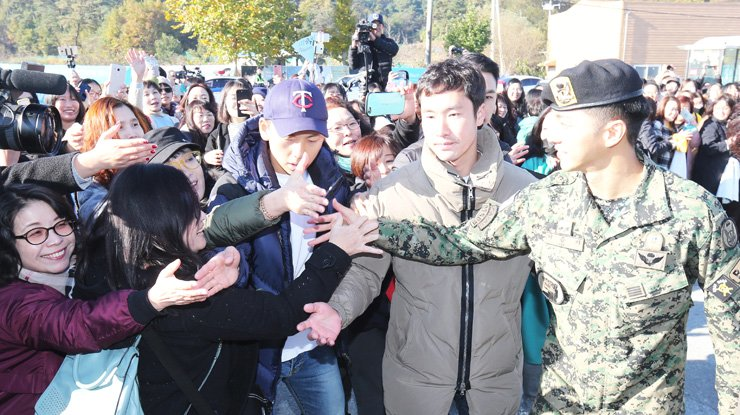 <span>Lee Seung-gi shakes hands with fans who came to see his discharge from the mandatory military service. / Yonhap</span><br /><br />