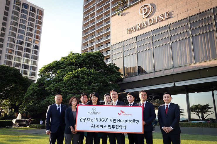 Park Myung-soon, fourth from left, senior vice president of SK Telecom's AI Business Division, poses with Park Jae-youn, fourth from right, president of Paradise Hotel Busan after signing a MOU at the hotel, Tuesday. / Courtesy of SK Telecom