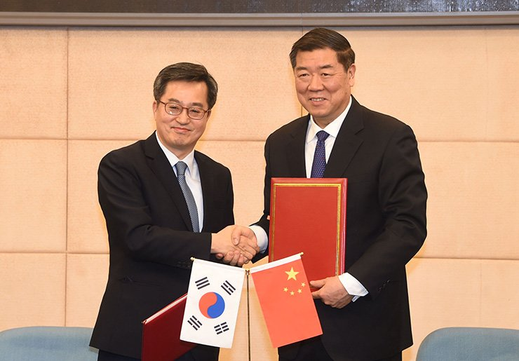 Finance Minister Kim Dong-yeon, left, and his Chinese counterpart He Lifeng shake hands after their meeting in Beijing, Friday. / Courtesy of Ministry of Strategy and Finance