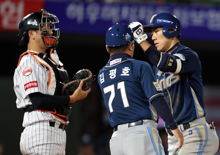 NC Dions' infielder Mo Chang-min, right, celebrates his solo home run with coach Kim Pyeong-ho, center, in the seventh inning against the Lotte Giants at Sajik Stadium in Busan on Wednesday. Mo pulled together four RBIs during the game. / Yonhap