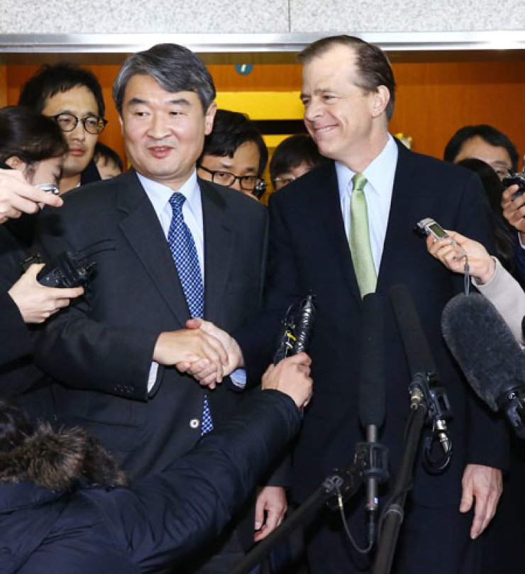 Cho Tae-yong, left, the Ministry of Foreign Affairs' special representative for Korean peninsula peace and security, and Glyn Davies, U.S. special representative for North Korea policy, shake hands during a media briefing held after a bilateral meeting at the ministry in Seoul, Wednesday. / Yonhap