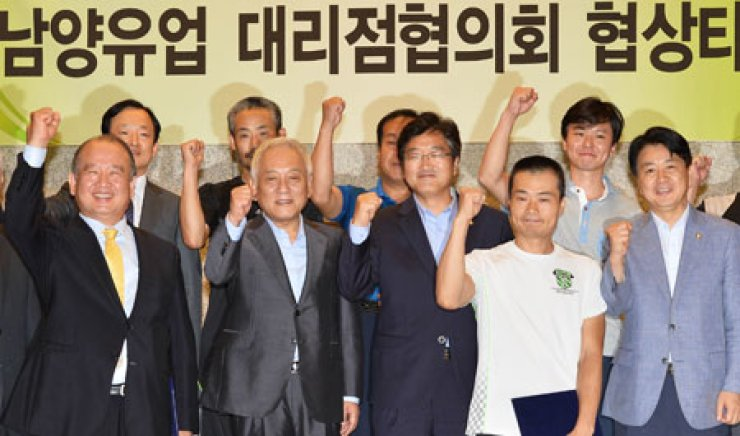 Namyang Dairy Products CEO Kim Woong, left, and Namyang Sales Agent Committee Chairman Lee Chang-sup, second from right, pose at LW Convention in downtown Seoul, Thursday, after they reached a settlement for compensation for losses caused by the firm's unfair business practices.The signing ceremony was also attended by the main opposition Democratic Party leader Kim Han-gil, second left, and the party's floor leader Woo Won-sik, third from left. / Korea Times photo by Shim Hyun-chul