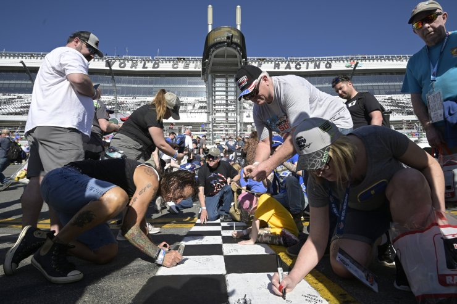 Fans leave their autographs on the start/finish line before the NASCAR Daytona 500 auto race at Daytona International Speedway, Sunday, Feb. 16, 2020, in Daytona Beach, Fla. AP