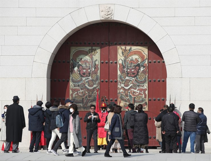 Visitors watch paintings on the main entrance of Gwanghwamun Palace in Seoul's Jongno District on Feb. 13. Yonhap