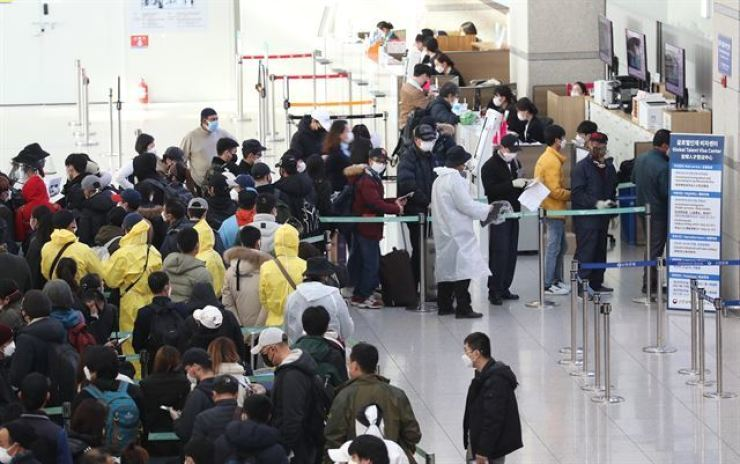 Undocumented foreigners stand in line to make voluntary reports on their status at Incheon International Airport in this March 2020 photo. Yonhap