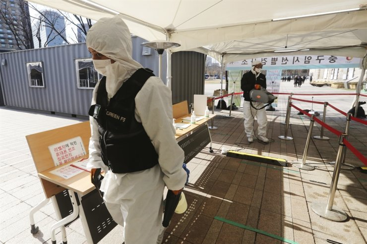 A man wearing protective suits sprays disinfectant as a precaution against the coronavirus during lunch time at a makeshift clinic in Seoul, Wednesday, Jan. 20, 2021. /AP