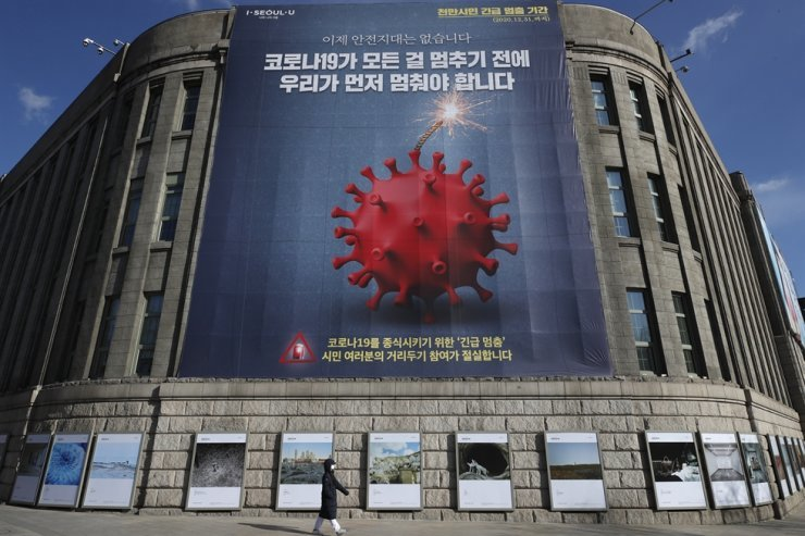 A visitor wearing a face mask as a precaution against the coronavirus walks near a banner emphasizing an enhanced social distancing campaign in Seoul, Wednesday, Dec. 30, 2020. AP