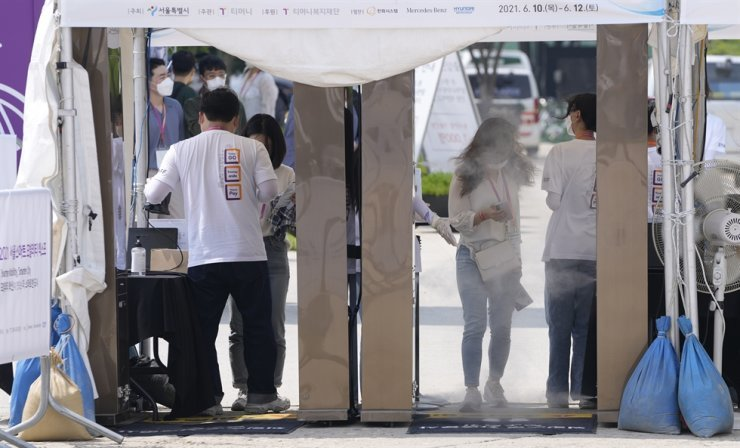 Visitors wearing face masks walk through a gate which sprays disinfectant as a precaution against the coronavirus at a venue for the Seoul Smart Mobility Expo in Seoul, June 10. AP-Yonhap