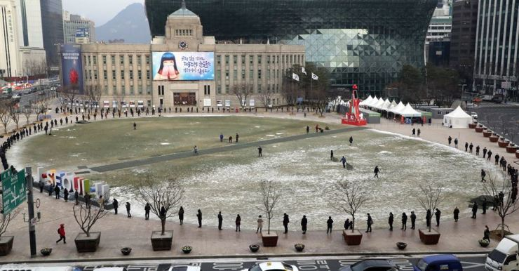People line up to receive COVID-19 tests at a makeshift testing center at Seoul Plaza in front of Seoul City Hall, Friday. Yonhap