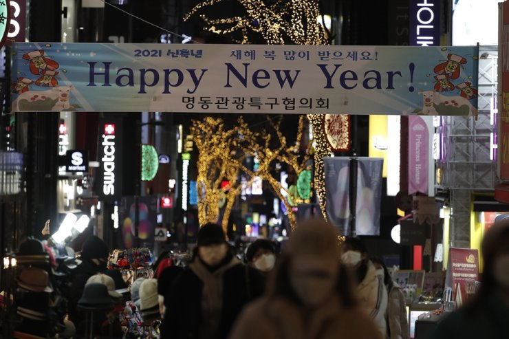 Visitors wearing face masks walk near a New Year banner at a shopping district in Seoul, Thursday, Dec. 31, 2020. AP