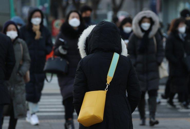 Pedestrians wearing coats cross the street in Seoul, Wednesday. /Yonhap