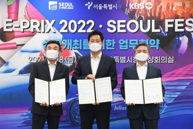 Seoul Mayor Oh Se-hoon, center, poses after signing the MOU for the Seoul E-Prix 2022 at the Seoul City Hall, Friday. / Courtesy of Seoul Metropolitan Government