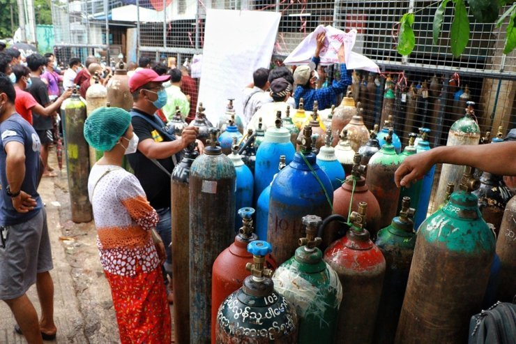 People wait to have oxygen tanks refilled outside the Naing oxygen factory at the South Dagon industrial zone in Yangon, Myanmar, July 28. AP-Yonhap