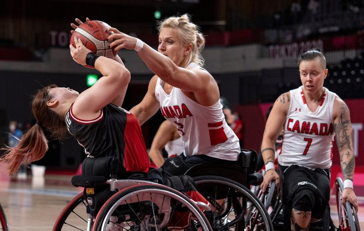 Japan's Amane Yanagimoto is challenged by Canada's Kathleen Dandenau during a wheelchair basketball preliminary match in Group A at the Tokyo 2020 Paralympic Games on Friday, Aug. 27, 2021, in Tokyo. AP