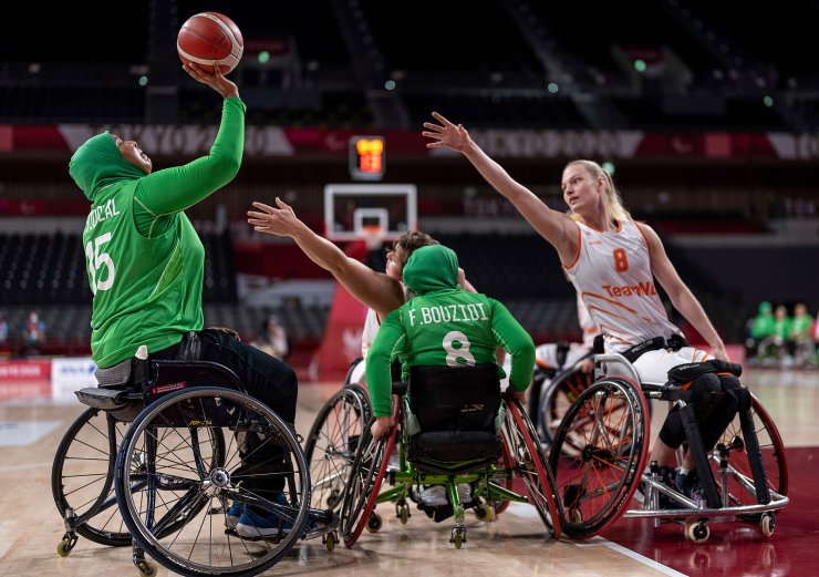 Nourhane Boublalm, left, of Algeria is about to shoot as her teammate Fatima Bouzidi (8) blocks the Netherlands defenders during the  wheelchair basketball Preliminary Round Group B game at the Tokyo 2020 Paralympic Games in Tokyo Friday, Aug. 27, 2021. AP