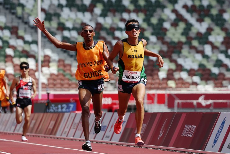Tokyo 2020 Paralympic Games - Athletics - Men's 5000m - T11 Final - Olympic Stadium, Tokyo, Japan - August 27, 2021. Yeltsin Jacques of Brazil and guide in action. REUTERS