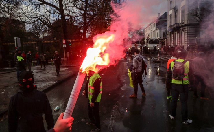 A 'yellow vest' (Gilet Jaune) protester holds a torch near the Royal Palace, during a demonstration on November 30, 2018, near major EU buildings in Brussels. AFP